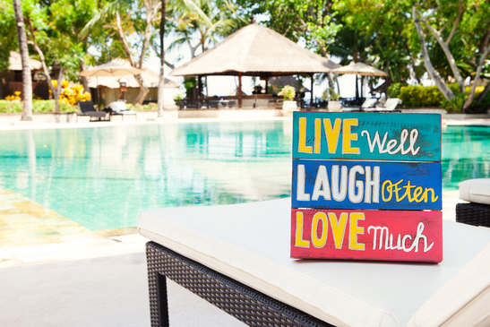 Inspirational Motivational Life Quote wooden board Live Well Laugh Often Love Much on summer, tropical swimming pool background Copy space.